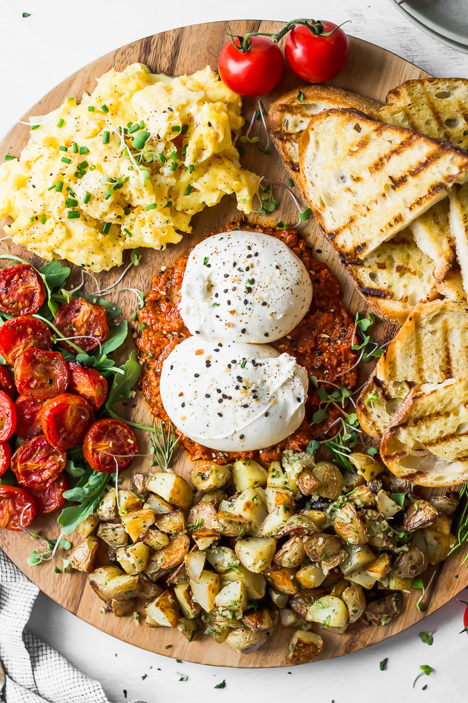 close up round wooden breakfast board with burrata, tomatoes, eggs, toast, potatoes