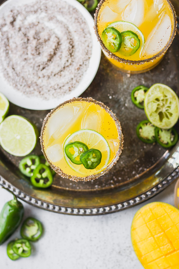 overhead mango margaritas with pepper salt rim, jalapenos, and lime on top of silver platter