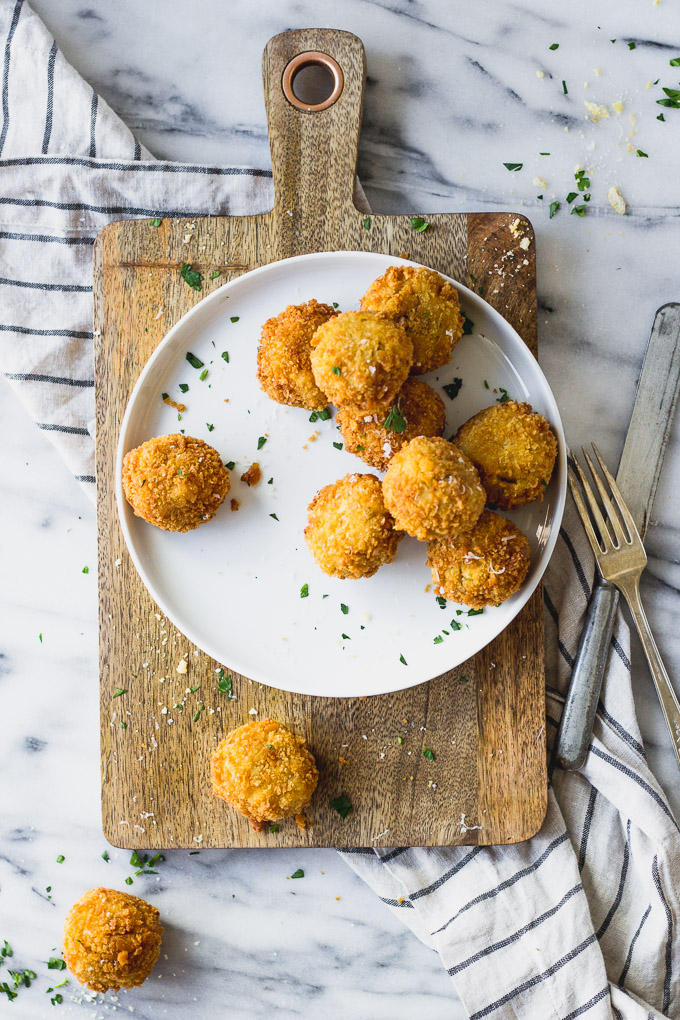 Scalloped Corn Arancini on plate and serving platter