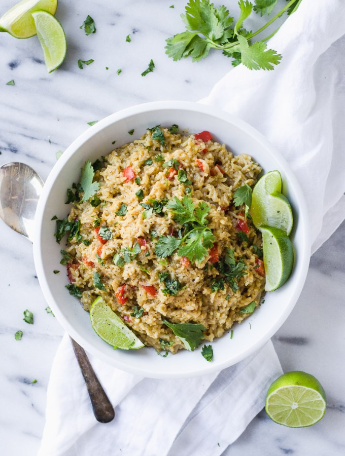 white bowl with cheesy mexican rice, limes, and cilantro