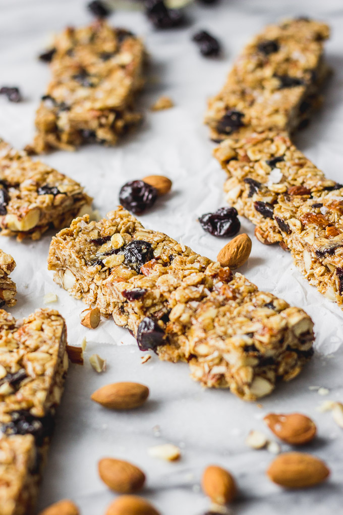 cherry almond granola bars spread out on white background
