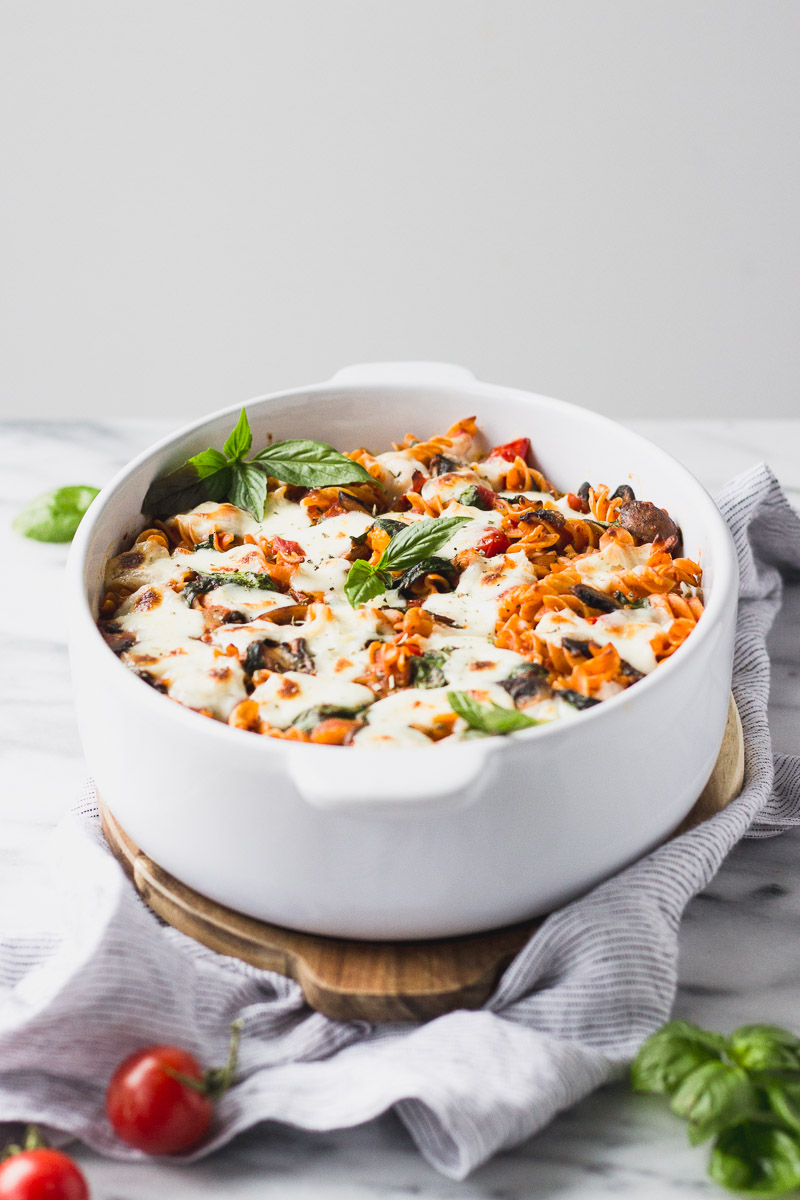 vegetable baked pasta with basil in white casserole dish
