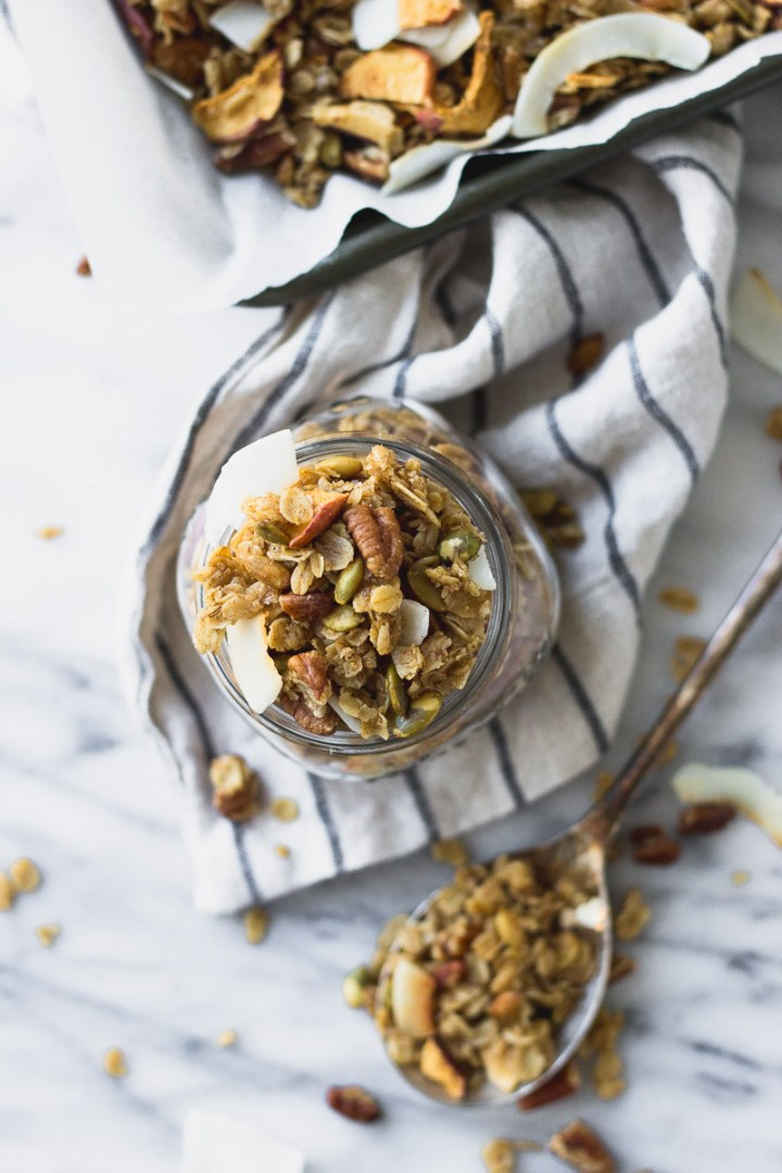 easy autumn spice granola on spoon and in jar by fork in the kitchen