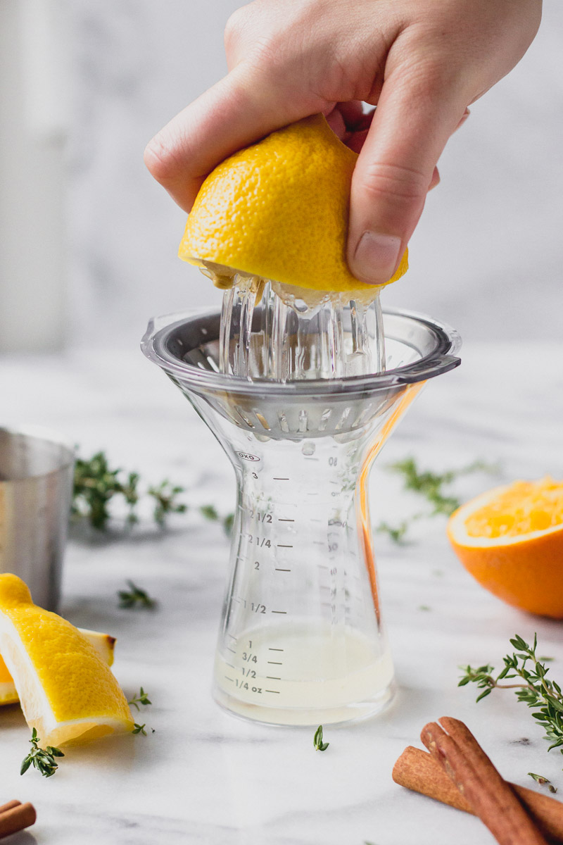 juicing a lemon for apple cider sangria using a citrus squeeze by fork in the kitchen