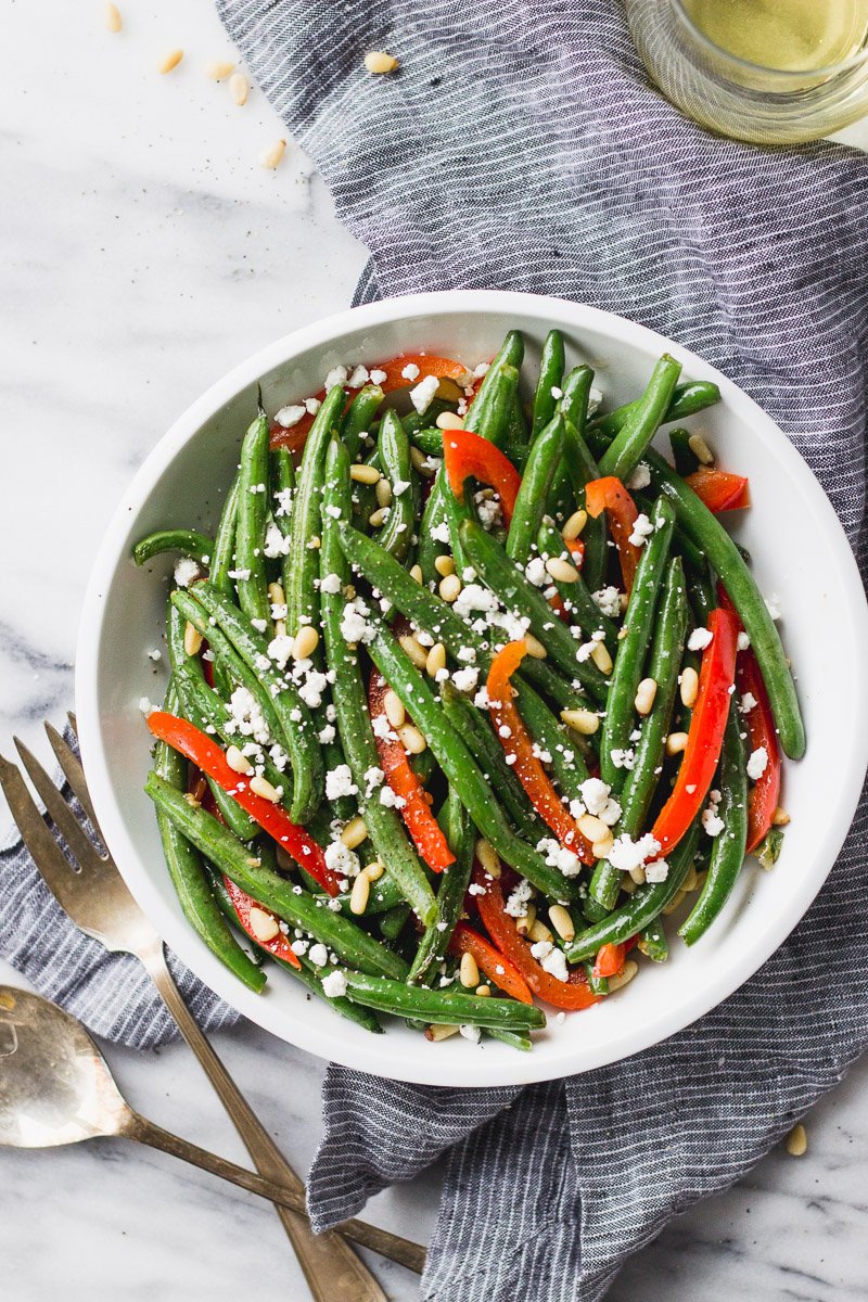green beans with red bell pepper, pine nuts, and goat cheese in white bowl with linen by fork in the kitchen