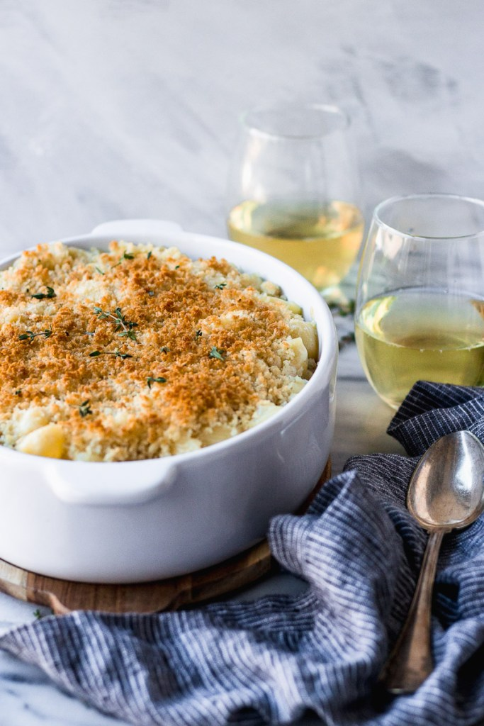 white wine mac and cheese with spoon and wine glasses by fork in the kitchen