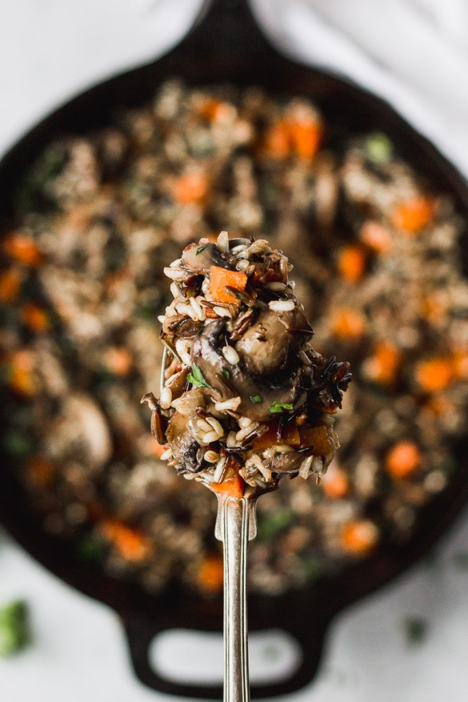 Herbed Wild Rice with Mushrooms on serving spoon by fork in the kitchen