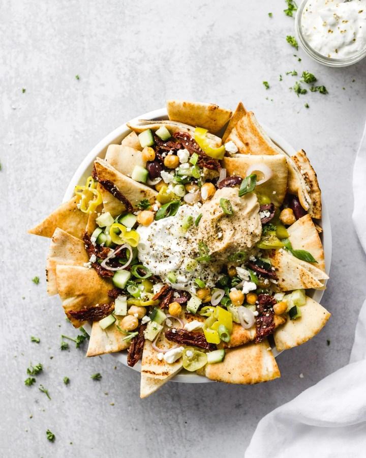 bowl of mediterranean nachos with dip by fork in the kitchen