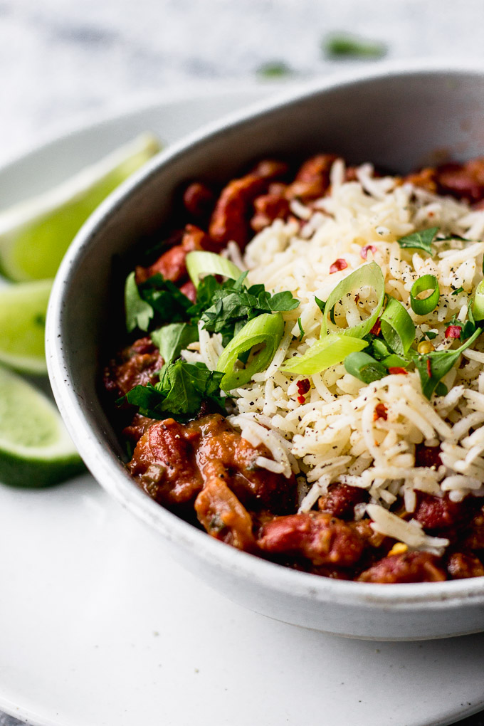 Vegetarian Red Beans and Rice in bowl with green onions and lime by fork in the kitchen
