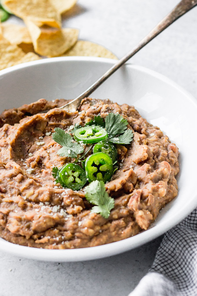 vegetarian refried beans in white bowl with jalapenos and cilantro by fork in the kitchen