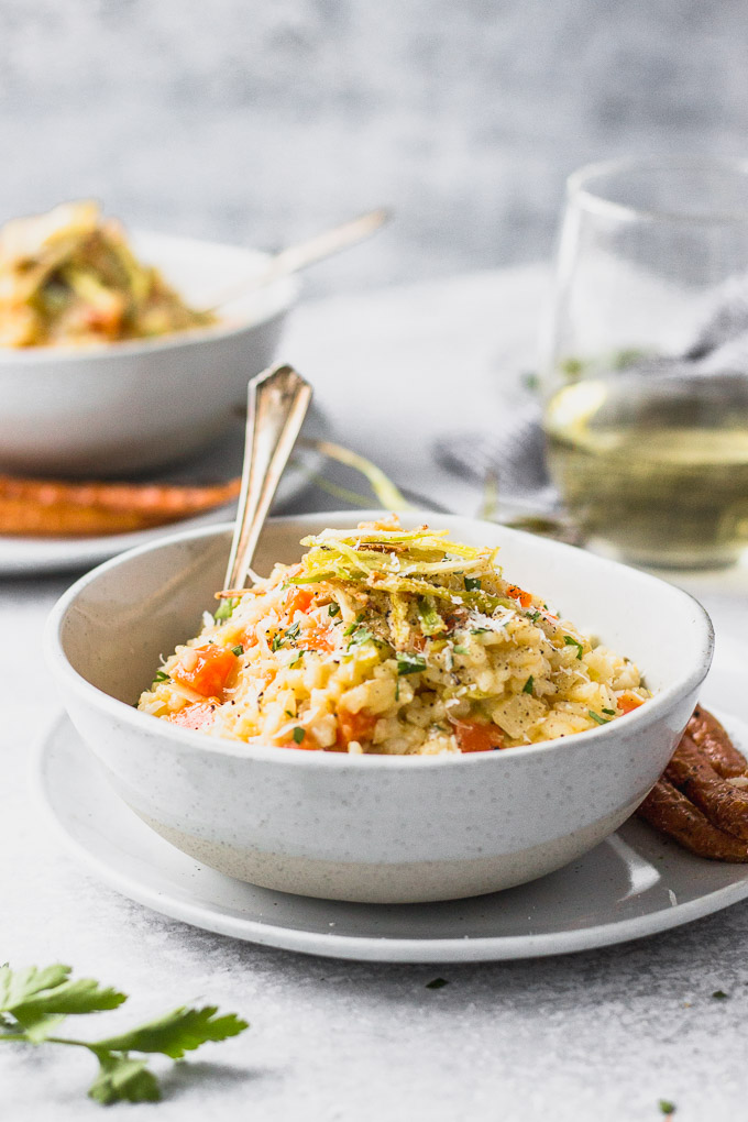 carrot leek risotto in bowls with blue linen by fork in the kitchen