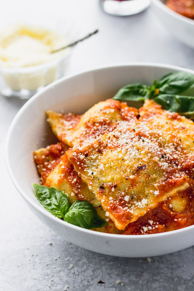 up close bowl of homemade cheese ravioli in white bowls with basil