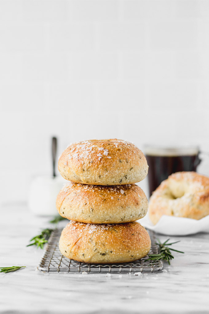 homemade rosemary bagels stacked with white linen