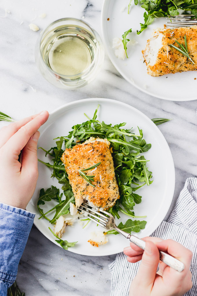 parmesan rosemary crusted cod on arugula with fork and hands