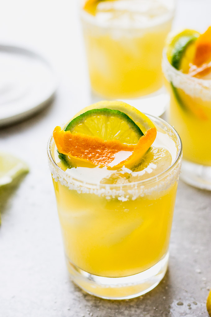 three citrus margaritas with salted rims and orange garnish