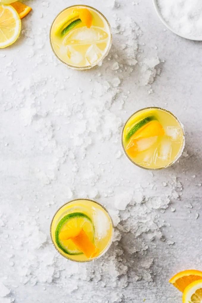overhead citrus margaritas with orange and lime garnish