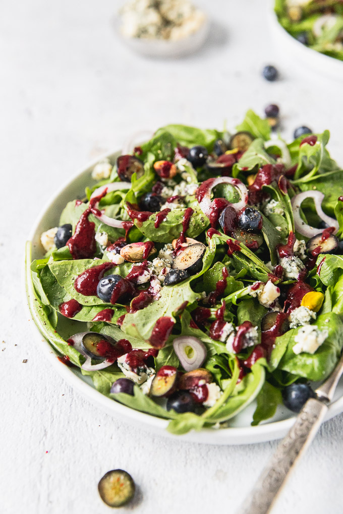 blueberry power salad on white plate with fork