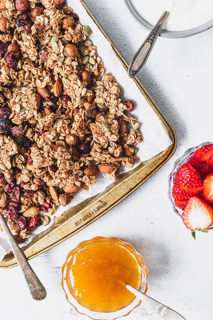 tray of cinnamon granola with apricot jam and strawberries in bowls next to
