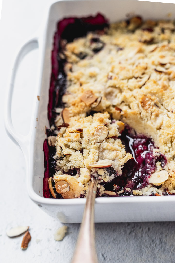 blueberry almond crisp in a white baker and spoons