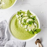 green cucumber soup in white bowls with linen next to them