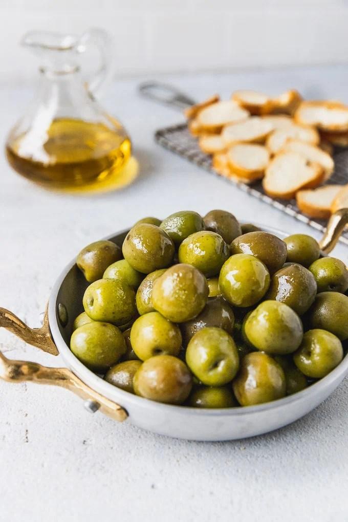 bowl of Castelvetrano olives next to olive oil and baguette crisps