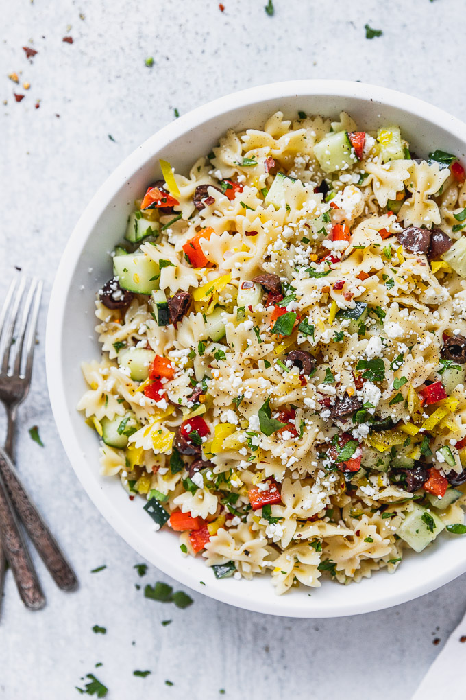 white bowl of bow tie pasta with mediterranean toppings