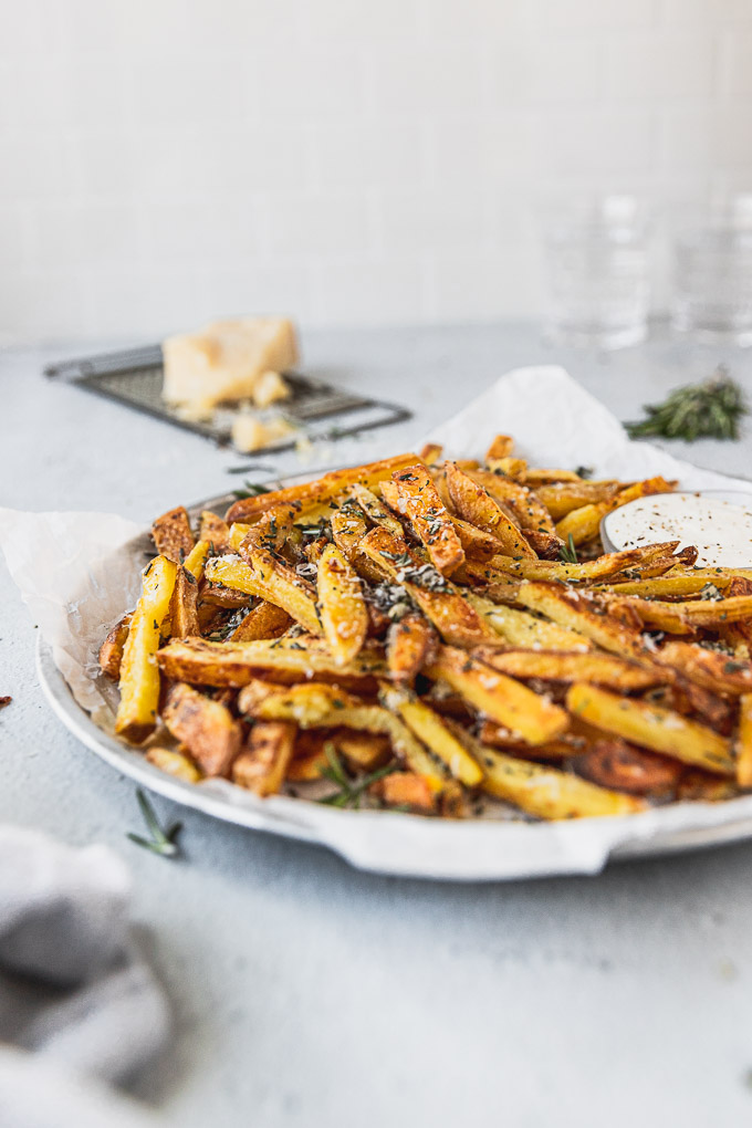 plate with crispy baked rosemary fries with parmesan