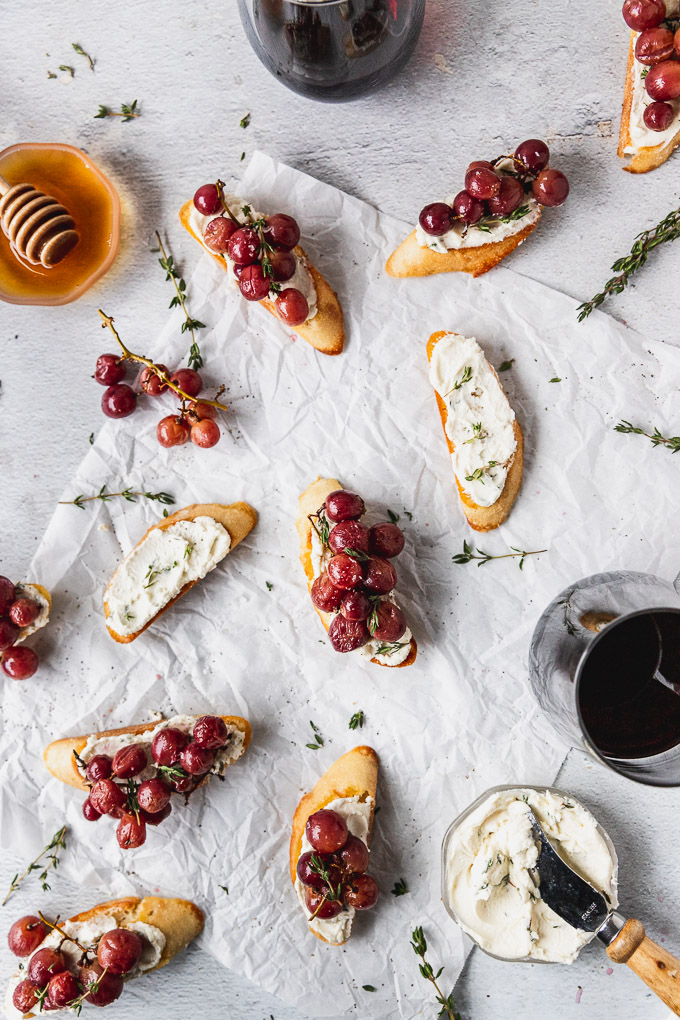overhead of roasted grapes on crostini with goat cheese and wine