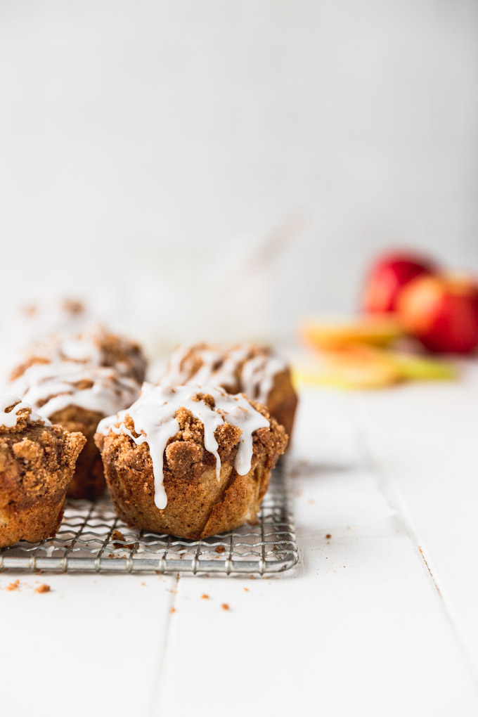 muffins on wire rack with white icing and apples in background