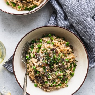 two bowls of mushroom risotto with forks next to blue striped linen and wine glass