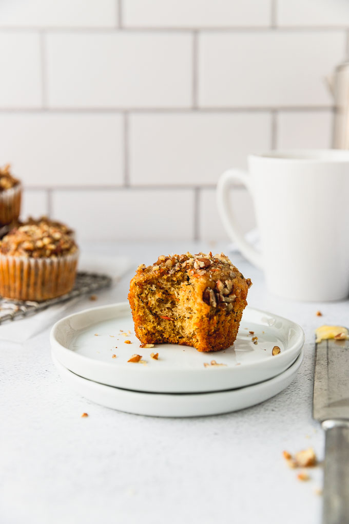 banana carrot muffin with bite out of it on white plate next to white coffee mug