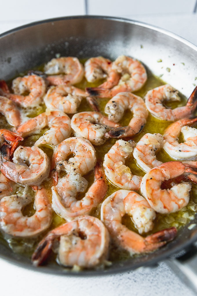 shrimp cooking in butter in a skillet