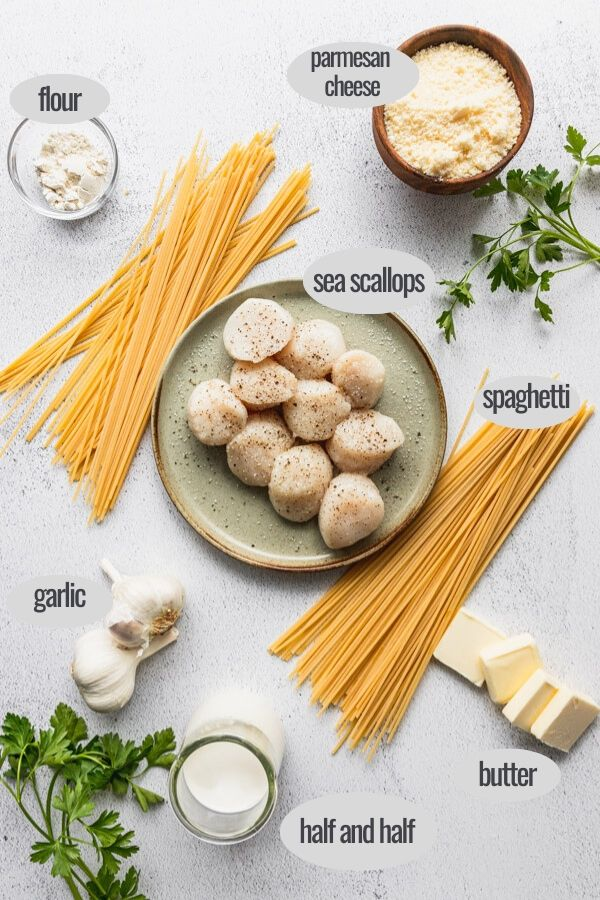 plate of raw scallops next to spaghetti noodles, garlic, parsley, and parmesan with butter slices and flour - the pasta ingredients laid out