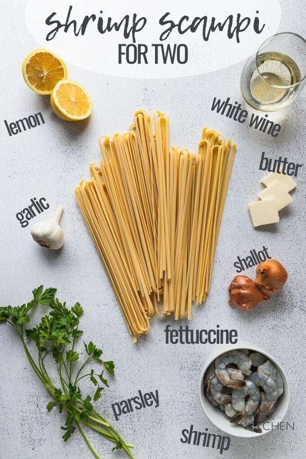 shrimp scampi ingredients laid out: pasta, butter, white wine, lemon, garlic, parsley, shrimp