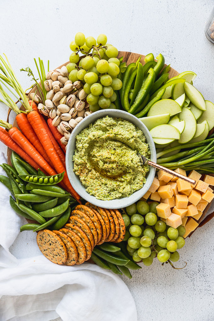 snack board with fresh vegetables and edamame hummus in the center with a spoon