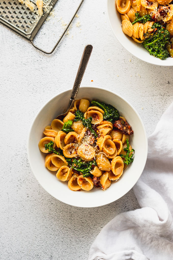 white bowl with orecchiette pasta next to another bowl and white linen