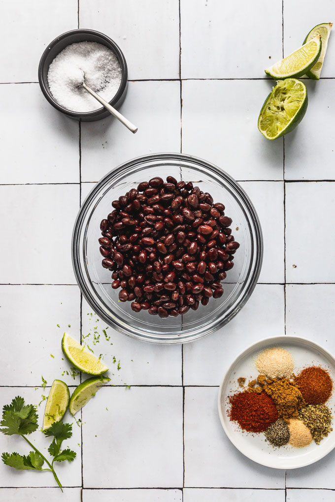 bowl of black beans next to salt bowl, limes, and plate of spices