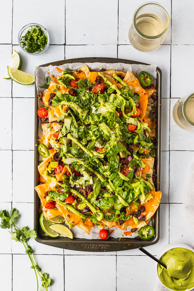 birds eye view of sheet pan with spicy black bean nachos topped with tomatoes, lettuce, and avocado drizzle next to cilantro leaves and avocado sauce, lime wedges, and two wine glasses