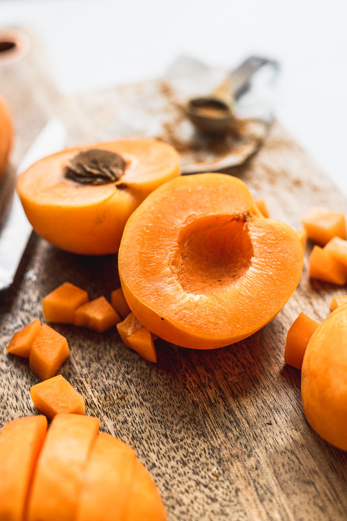 apricot cut open on wooden cutting board