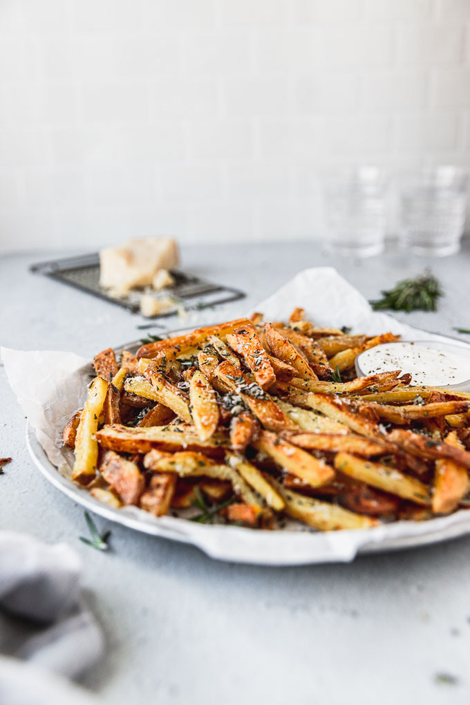 side view of silver tray with Crispy Baked Rosemary Garlic Parmesan Fries, a wedge of parmesan in the background, and two water glasses