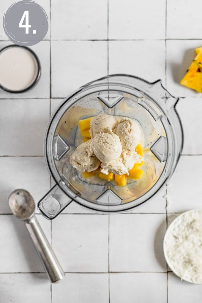 ice cream scoops in blender with pineapple for pina colada milkshake