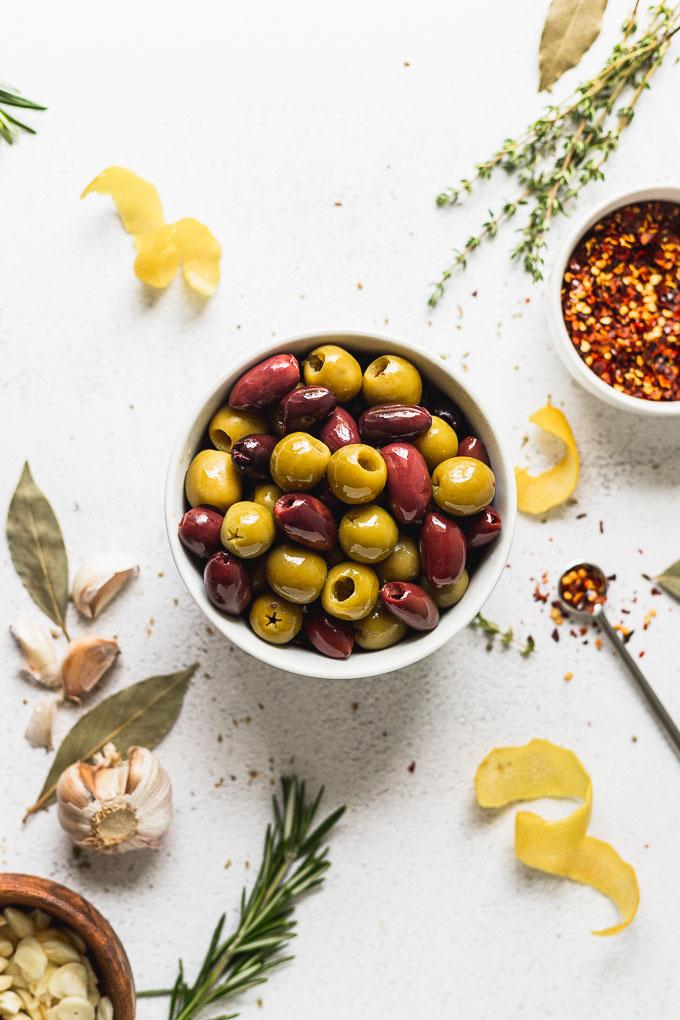 ingredients for marinaded olives laid out: olives, red pepper flakes, bay leaves, garlic, and lemon with fresh herbs