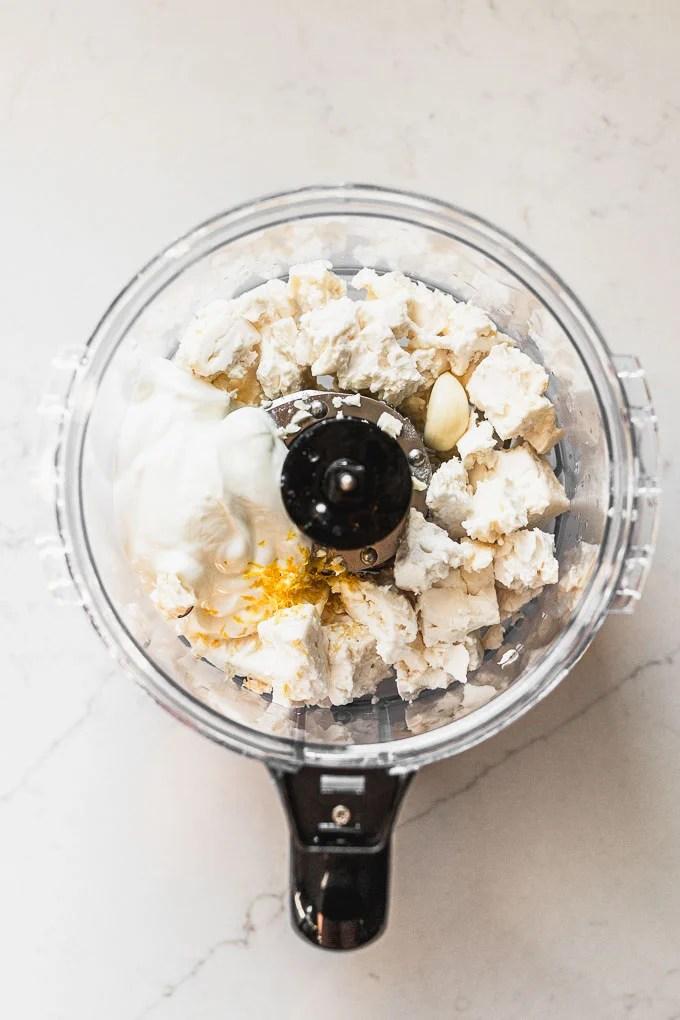 food processor with feta chunks, greek yogurt, lemon zest, and garlic cloves