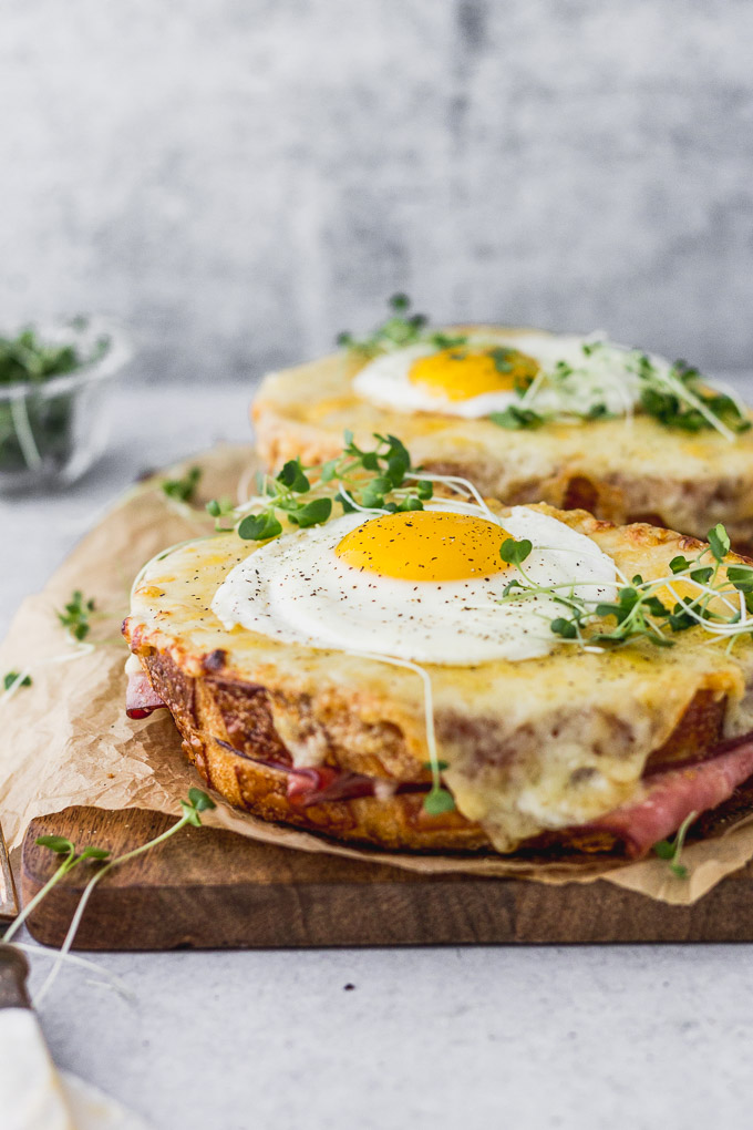 two croque madame sandwiches on wooden board with microgreens