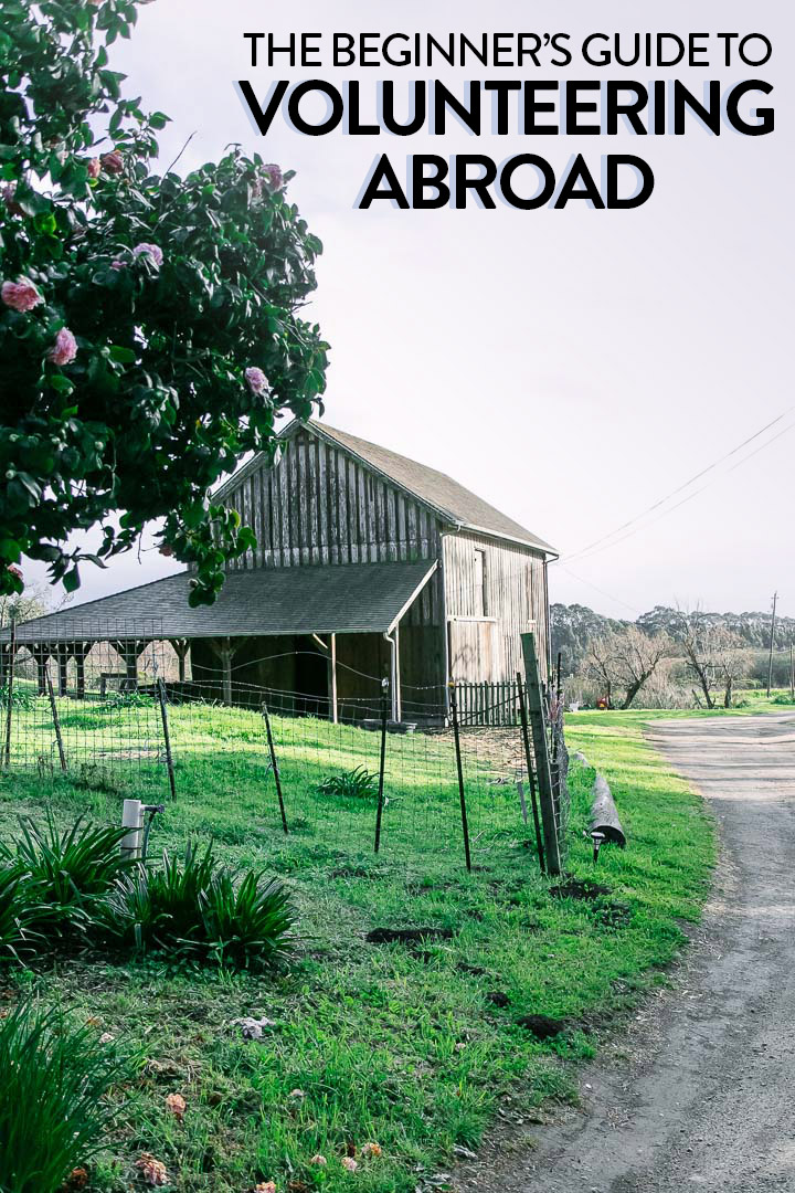 "A barn beside a dirt road and the words ""the beginner's guide to volunteering abroad"" in black writing."