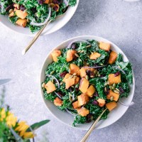 Two white bowls with a fall kale salad on a blue table with orange flowers.