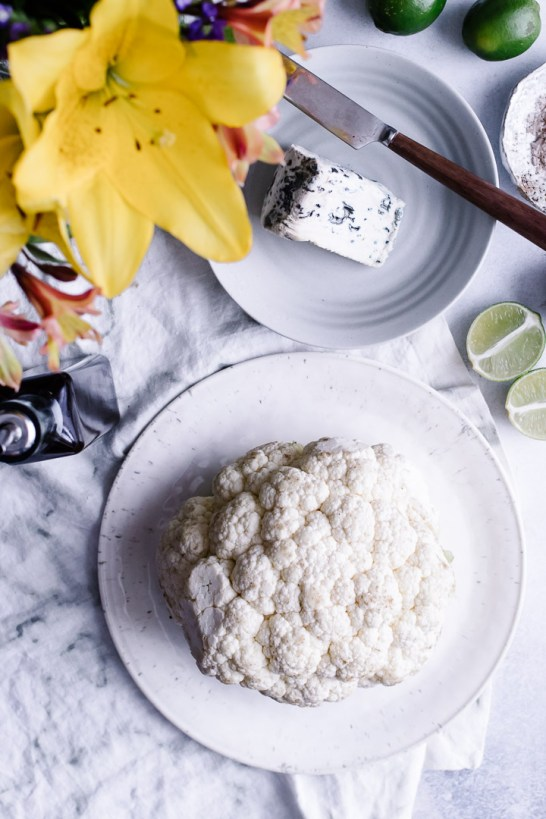 A white plate with a head of cauliflower and a side of blue cheese and cut limes.