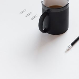 Coffee, pencils, and paperclips on a table.