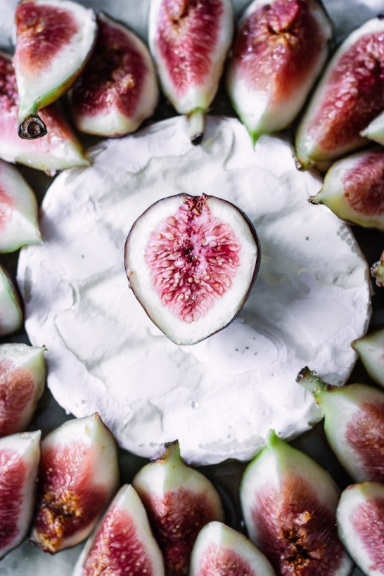 A close up shot of figs on top of brie.