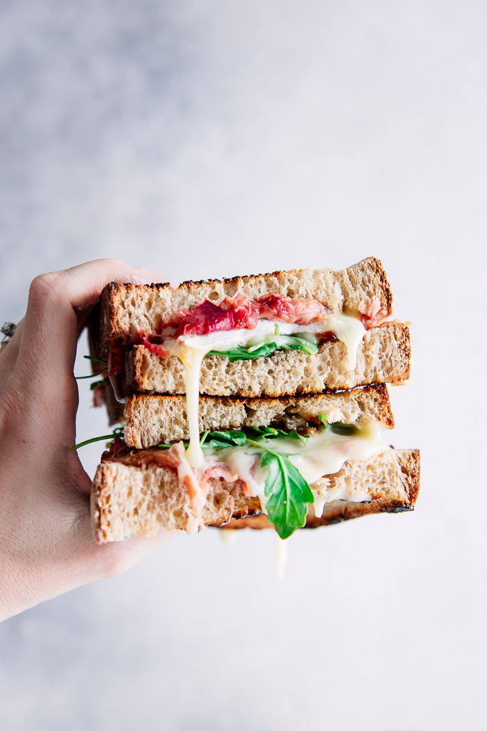 A hand holding a cut brie and rhubarb sandwich with oozing cheese.